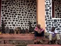Mission Bandja. les serviteurs du chef assis sur les marches du palais colonial © Estelle Vanneste